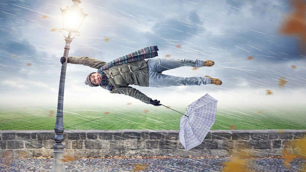 Immunsystem-Cover: Mann hängt bei Sturm an der Laterne waagerecht im Wind.